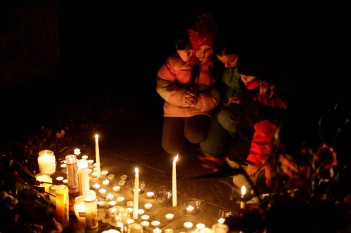 FAMILY PRAYS AT MAKESHIFT MEMORIAL OUTSIDE CATHOLIC CHURCH IN NEWTOWN